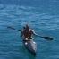 Ein Mann sitzend im schwarzen Kajak paddelt im Meer