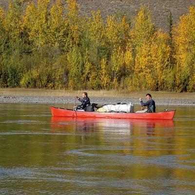 Eine Frau und ein Mann im roten Kanu am Yukon River in Kanada