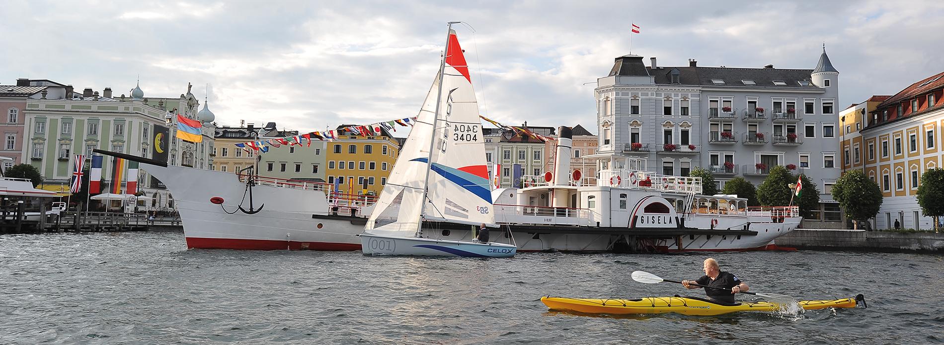 ein Kajakpaddler, Dampfschiff Gisela, ein Segelboot, Stadt Gmunden am Traunsee