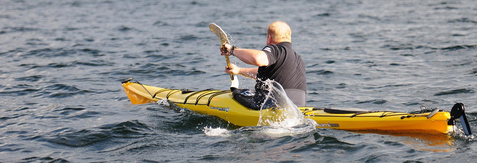 Ein Mann der im gelben Kajak am Traunsee paddelt