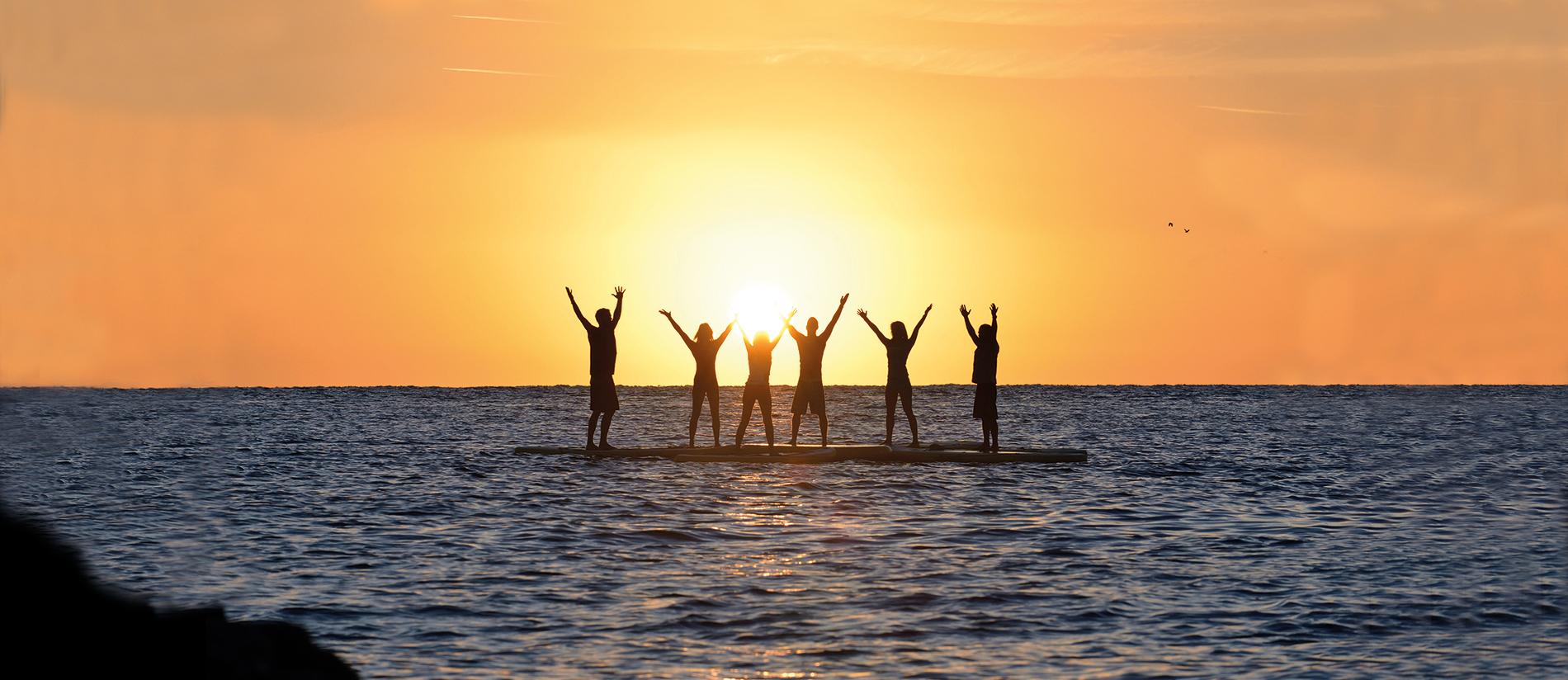 sechs glückliche SUP Paddler - stehend am SUP Board und Sonnenuntergang-Stimmung
