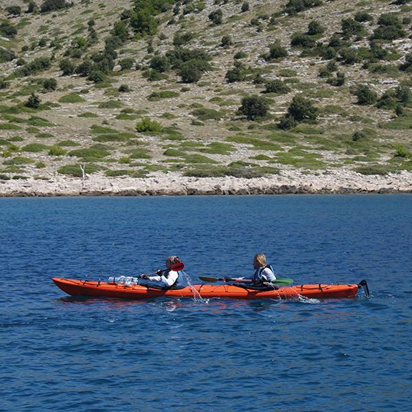 zwei Personen paddeln in einem roten Kajak entlang der Küste im Meer